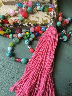 This is one of the most FUN necklaces you will wear...a gem to add to your ever growing accessory collection!!  I have hand knot these Czech crystal beads and gemstones using orange silk cord. Every time I look at it different colors pop out!! Ive made the tassel using cotton floss. Its bright color is what makes this such a fun accessory and unique. This is a great BoHo summer piece!!  The necklace measures 34 with a 5 tassel. Original list date June 29, 2016.