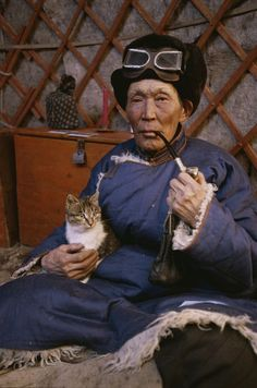 'An elderly Mongolian man relaxes with his pipe and cat inside his ger.' by National Geographic