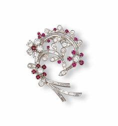 A DIAMOND AND RUBY CLIP BROOCH    Designed as a brilliant-cut diamond floral spray accented by cabochon rubies to the baguette-cut diamond stems, mounted in platinum and white gold, 5.0 cm high, with French assay marks for platinum and gold