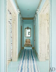 A hallway, painted in Benjamin Moore's Clear Skies, is lined with plaster palm trees. Rugs from IKEA were stitched together to make the runner.