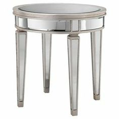 "Mirrored side table with a champagne silver leaf finish.  Product: Side tableConstruction Material: Mirrored glass and woodColor: Champagne silver leafDimensions: 27"" H x 25.75"" Diameter"