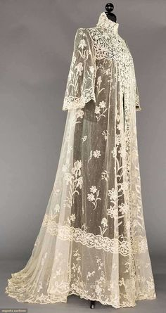 "BRUSSELS LACE PEIGNOIR, 1905  Lot: 188 May 9, 2017 - CATALOG SALE Sturbridge, Massachusetts  White cotton tulle w/ floral appliques of iris, lillies-of-the-valley, etc., edging & insertions of Brussels lace guipure, bell sleeves & trained, B 34"", L 63""-80"", excellent."