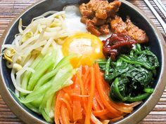 Bibimbap | White Rice, Sauteed Spinach with Soy Sauce, Sesame Oil and Garlic, Matchstick Carrots, Julienne Cucumbers, Bean Sprouts, Thinly Sliced Pork, Steak or Chicken Seasoned and Sauteed, Eggs Sunny Side Up, Srirachi or Garlic Chili Sauce