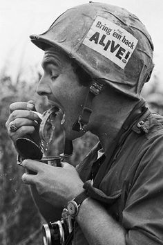 "Vietnam War: War photographer eating canned fruit (?) The sign on his helmet has been altered to signify his own personal desire to be delivered back home alive. Death in Vietnam was often described as ""more poignant"" than deaths in previous wars -- one more little piece of evidence about the VM war's deeply divisive nature."