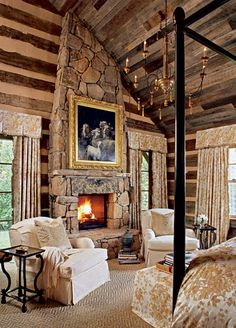 Cozy yet glamorous log cabin bedroom with stone fireplace, four-poster bed and chandeliere