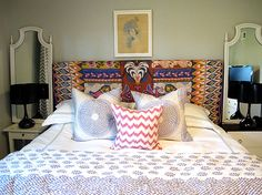 bedrooms - gray walls ethnic blanket headboard white hotel bedding lilac stitching white lilac shams quilt white pink wavy pillow mismatched nightstands  white farmhouse table glossy black gourd lamps white mirrors