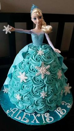Elsa doll cake with buttercream rosettes and blue sugar for ice on the cake board.