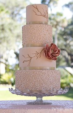 soft coral 4 tier wedding cake with pressed flowers and deep coral centerpiece flower by the pastry studio