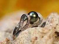 Perle de culture de Tahiti légèrement en forme de poire de couleurs vert-jaune-rose de qualité B diamètre 9 millimètres montée sur une bague en argent rhodié avec ses pierres zirconium incrustés. Cette bague est faîte pour un doigt de taille 62.