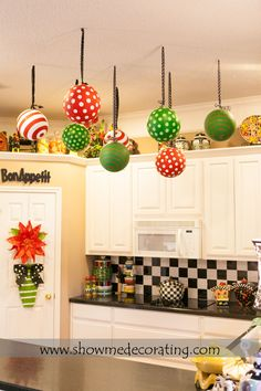 Christmas decor.  Oversized Christmas ornaments tied with coordinating ribbon suspending from the ceiling leaves the room decorated from top to bottom.