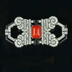 An art deco coral, enamel and diamond brooch, late 1925, the openwork plaque set at the centre with an octagonal buff top sugarloaf coral, flanked by black enamel L-shaped motifs and pierced curlicues millegrain-set with old brilliant and single-cut diamonds and with black enamel terminals, French maker's mark and numbered 3842, French assay mark, length 6.8cm.