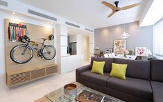 How to Store and Display Your Bikes in a Small HDB Flat: Displayed in full glory, the bicycle is displayed against a custom-made wooden shelf, along with the homeowner's bike accessories and cycling accolades.