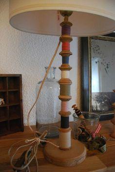 pied de lampe avec abat-jour faite d'une série de vieilles bobines de fils en bois.