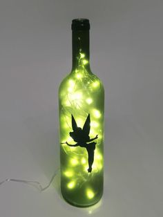 Recycled wine bottle made into a lamp with Tinkerbell from Peter Pan on the front. This light makes a great decoration for any home or dorm and a great anniversary, wedding, birthday, graduation or holiday gift! This is a small (regular size), green wine bottle but larger bottles, different shapes, and different colors are available (see image above). The lights inside can either be regular two prong plug-in lights (US plug) or battery powered lights. (See image above. Batteries not…