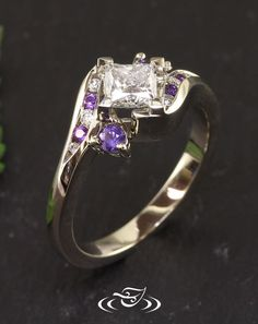 Custom 14kt warm white gold wrap style mounting holding a 4-prong set princess cut 0.61ct center diamond. Channel set in wrap style arms, alternating round cut purple sapphire and diamond accent stones.