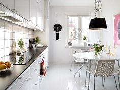 kitchen shiny white floor and walls white cabinets black counter white tile dark grout