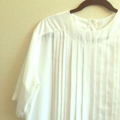 White Boxy Top with Vertical Pleating This vintage shirt has an oversized/boxy feel. The vertical pleating on the front is gorgeous, and the back has a four button closure. It is such a lovely vintage blouse in grand condition! Pierre Cardin Tops Blouses