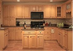 Dark granite counters with maple cabinets and dark hardware. Nice, except for the wallpaper. Blech! ~ http://kitchencabinetpictures.com/image/43/Maple-Kitchen-Cabinets-Pictures-5.jpg