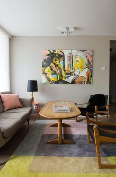 GRÅTT, BRUNT OG LYSROSA: Komfortdelen av stuen er innredet med safaristoler fra en dansk bruktbutikk, et arvet sofabord og et gulvteppe fra Hay. Bordlampen er satt sammen av en ny skjerm og en gammel fot fra norske Høvik Lys. Maleriet er ved Helene Strand.
