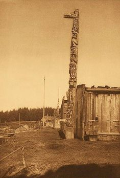 Cathedral Grove | Totem Pole Websites: The Seattle based American photographer Edward S. Curtis used Tsaxis as the base for his monumental 1915 book of Kwakwaka'wakw photos. Among them is a photo of a house pole at Tsaxis (right). It shows a pole carved by Charlie James and raised by David Hunt in front of his house to honour his grandmother.