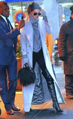 Kendall Jenner wears a turtleneck sweater, long coat, leggings, thigh-high boots, aviator sunglasses, and a fur satchel