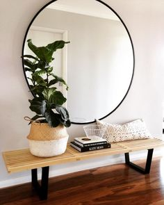 Large round mirror above a wood bench