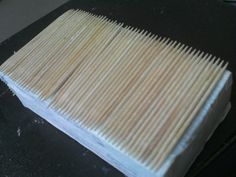 una vez forradas las cajas con papel de cocina, o cualquier otro que tengas a mano, encolamos y vamos pegándole los palillos o el material que hayas elegido