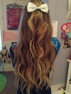 Long wavy blonde hair with a little white bow up top.