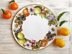 Tortiera in porcellana decorata con una ghirlanda di frutta e fiori in colori autunnali. Questo piatto può essere usato per portare elegantemente in tavola un dessert o può essere appeso alla parete di un soggiorno o una cucina per abbellire la casa. La tortiera può essere personalizzata con le vostre iniziali, un nome o una scritta dipinta a mano al suo interno. DIMENSIONI: diametro del piatto: 32 cm. Oggetto interamente dipinto a mano su porcellana bianca italiana di prima qualità senz...