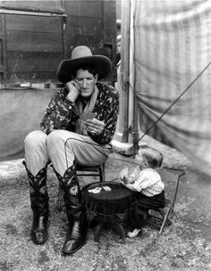 Jack Earl, the Cowboy Giant and Midget Mite playing cards behind the tent line of Ringling Bros. show. (1934)