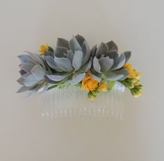 This succulent hair comb measures 4.5 inches long. It is made with Aeonium Kiwi succulents, and for a touch of color yellow and orange Mojave daisies were used. It may be created with purple or blue succulent and pink or white bloom or any other colors.  Custom options available