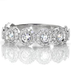 Elegance - Elegance features seven larger round brilliant diamonds, each surrounded by a dazzling halo of smaller diamonds. The larger diamonds are set in a bright cut milgrain bezel, creating a seamless transition into the halo.  The petite diamond halos surrounding each bezel gives this design a very unique and timeless look.