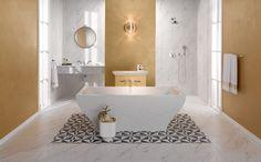 Cuarto de baño con motivos dorados y bañera exenta