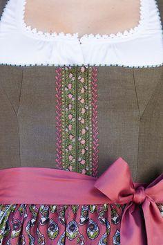 Feines Detail am Gössl Dirndl HEISSA, KATHREINERLE  Die Blätterranken am Leinenleib sind ein geketteter Federstich mit handgesticktem Blütenabschluss.