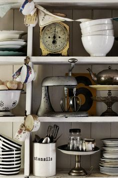 A vintage hand-crank kitchen mixer takes pride of place among other kitchenware.