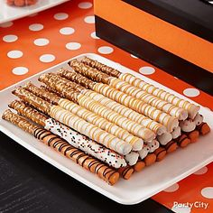 Super Easy Halloween Treats - Dip Pretzel Rods in white and orange melting chocolate. Drizzle with contrasting color and use sprinkles for a more festive look!