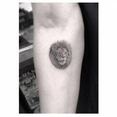 Pequeño tatuaje de estilo fine-line de la cabeza de un león...