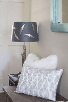 A navy lampshade is elevated to elegance with the addition of falling feathers cut from copper contact paper. Get the tutorial at Mountain Modern Life.