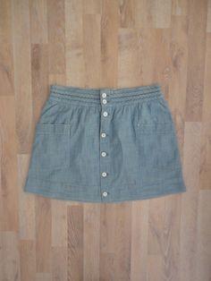 Pollera de jean azul claro con jean trenzado en la cintura y botones y bolsillos al frente #TommyHilfiger #ModaSustentable. Compra esta prenda en www.saveweb.com.ar !