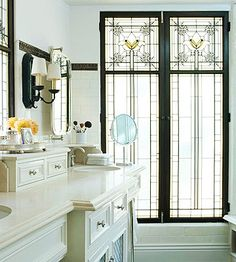 Stained-glass windows, original to the master bath of this 1920s home, play a big role in the remodeled version and brighten a neutral color scheme. Sunlight bounces off reflective surfaces, creating jewel-like reflections on the shower door and vanity.