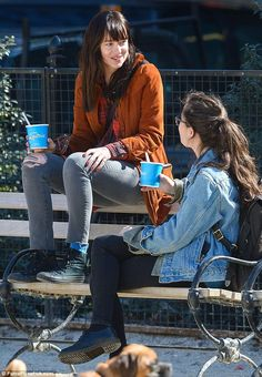 Casual: Dakota then stopped and sat on a park bench to finish off her sweet treat while she chatted with her brunette friend