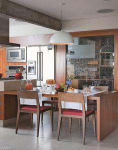 """Após a demolição da parede que separava a cozinha da sala, restou uma viga. """"Como ela ficaria muito evidente, resolvemos descascá-la e deixar o concreto aparente, textura que acaba valorizada pela madeira e pelas cores da cozinha"""".:"""
