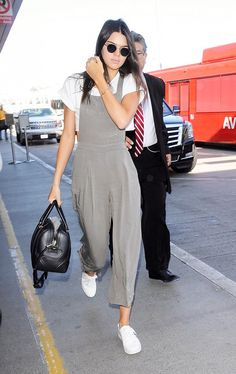 Kendall Jenner wears a cropped white t-shirt, neutral jumpsuit, white sneakers, round sunglasses, and a Givenchy duffle bag