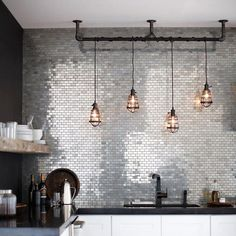 Such a cool kitchen … stainless metal mosaic tiles, aged bronze cage pendant lights, an adjoining wall painted chalk-board black + counter, tapewear also in black (like the added contrast of the reclaimed wood shelf ) | via Home Depot x debra follow on bloglovin'