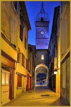 Photo à la tombée de la nuit de la rue Soubeyran dominée par la porte du même nom, à l'entrée Nord du coeur historique de Manosque, dans , dans le département des Alpes-de-Haute-Provence en région Provence-Alpes-Côte d'Azur. Photos de Manosque.