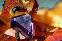 """underthescopemin: """"Fluorite, Quartz A small octahedral crystal cube of purple Fluorite,  red prisms of quartz with a group of mineral tourmaline related, dark green. Gianfranco Ciccolini's Photo"""""""