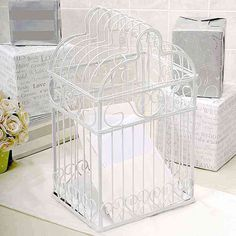 "Give your guests a fun spot to place their wedding well wishes with this splendid Birdcage Card Holder. With its sturdy frame and elegant scrolled heart design, it will be the perfect touch to any wedding gift table! The white metal frame is designed to contain cards and monetary gifts offers. Top lifts off for easy card removal.    Details:  Size: Measures 10"" by 8"" by 16 1/2 inches tall.  Materials: Sculpted white metal"