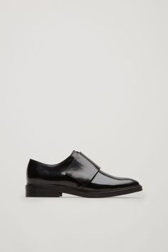 A clean silhouette with minimal detailing, these brogue style shoes are made from smooth, shiny leather. Designed with a simple strap with a modern Velcro fastening, they have a stacked heel and lightly cushioned insoles.