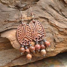 "Stylized Copper Peace Signs with faceted pink stone dripping from below. A wonderful mix of Copper with touches of silver. These fun earrings approximately 2.25"" long. The earrings hang from embellished Copper Earwires. See more Finished Jewelry and Components [HERE](https://www.etsy.com/shop/KristiBowmanDesign?ref=s2-header-shopname) in my Etsy Shop."