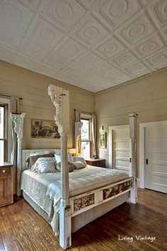 They made this bed from old porch columns and doors...love the ceiling tiles!